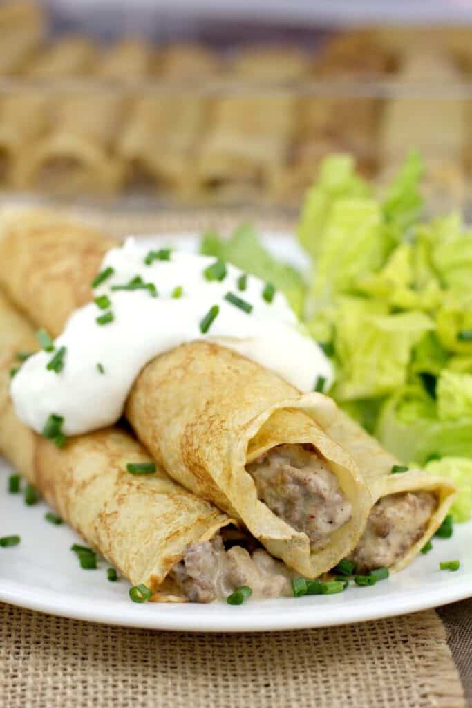 beef stroganoff crepes on a dish, topped with sour cream with a side of salad