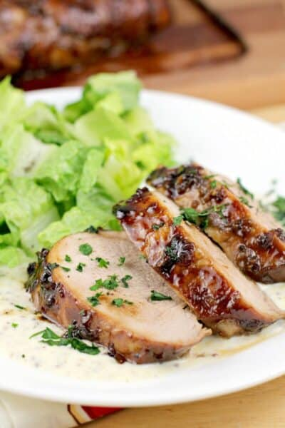 sliced pork medallions with bourbon glaze, on white serving plate with salad