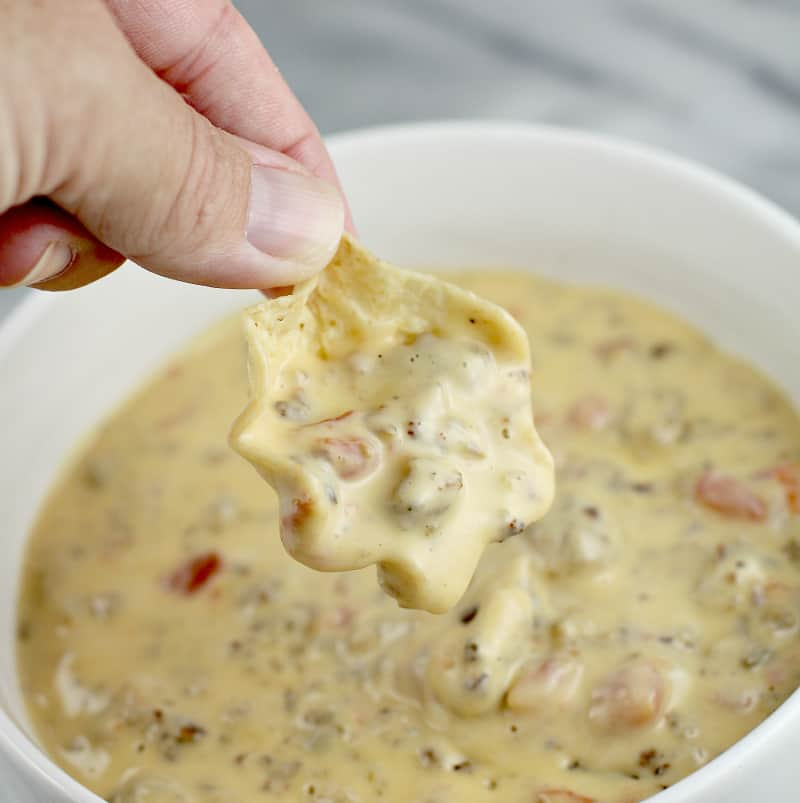 Close view of hand holding a scoop tortilla chip with queso over a bowl full of queso