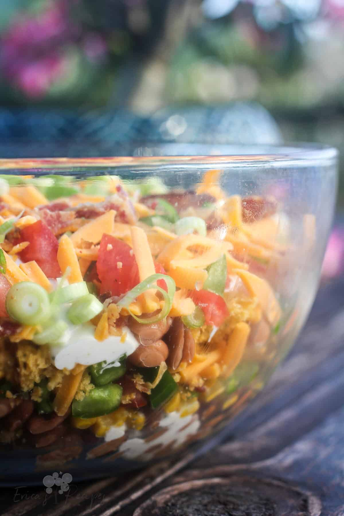 side view into glass bowl showing layers of cornbread salad