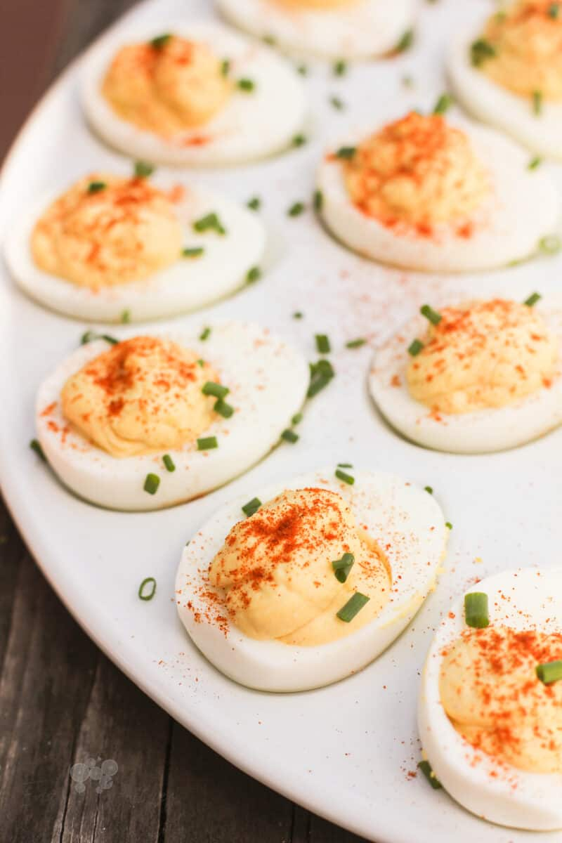 prepared deviled eggs topped with chives on a white serving platter