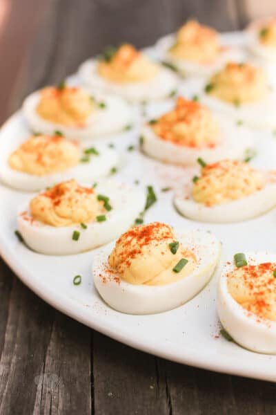 side view deviled eggs topped with chives on a white serving platter