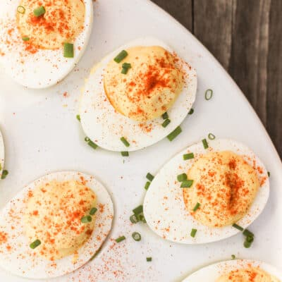 top down view of deviled eggs topped with chives on a white serving platter
