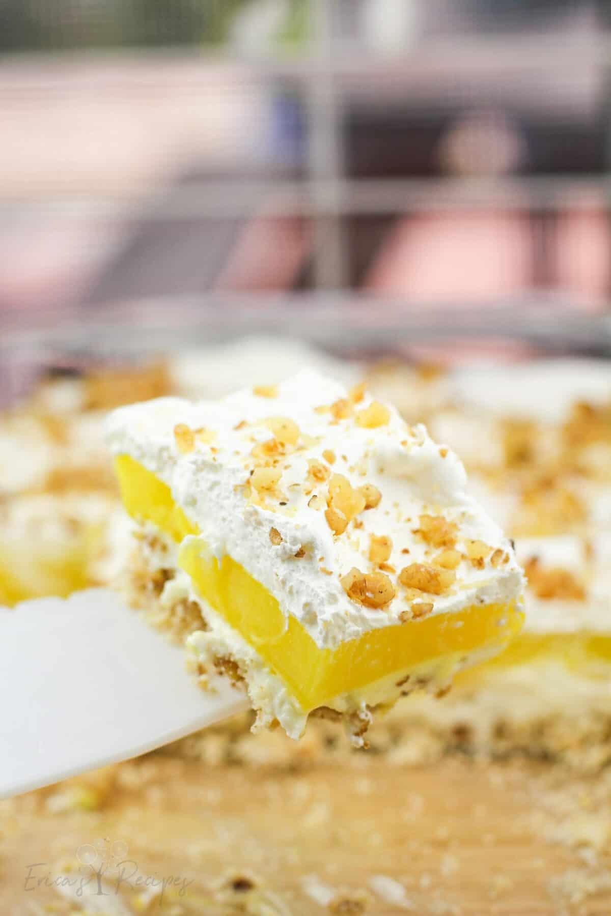 white pie server holding up portion of lemon delight