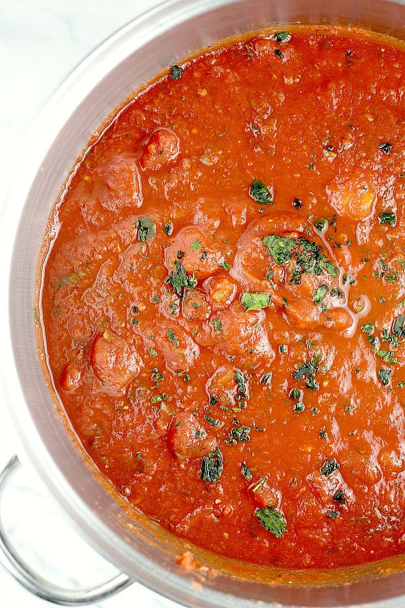 Top down view into the pot to show the finished canned tomatoes sauce; fresh herb is sprinkled on top