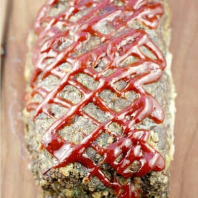 whole cooked best meatloaf ever on a wood board showing the criss-cross ketchup mixture on top