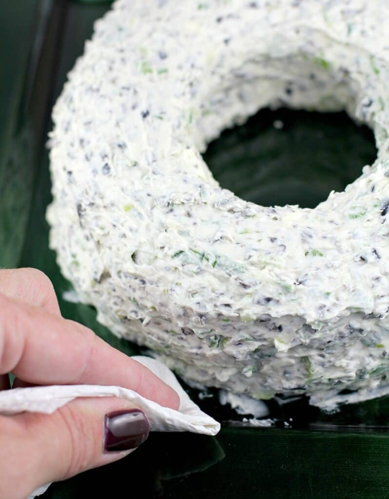 view of a hand holding a paper towel, removing smudges of dip from the plate after the christmas cheese wreath has been formed