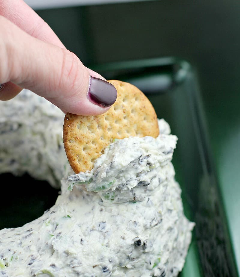 side view showing a person scooping up dip from the side of the cheese wreath