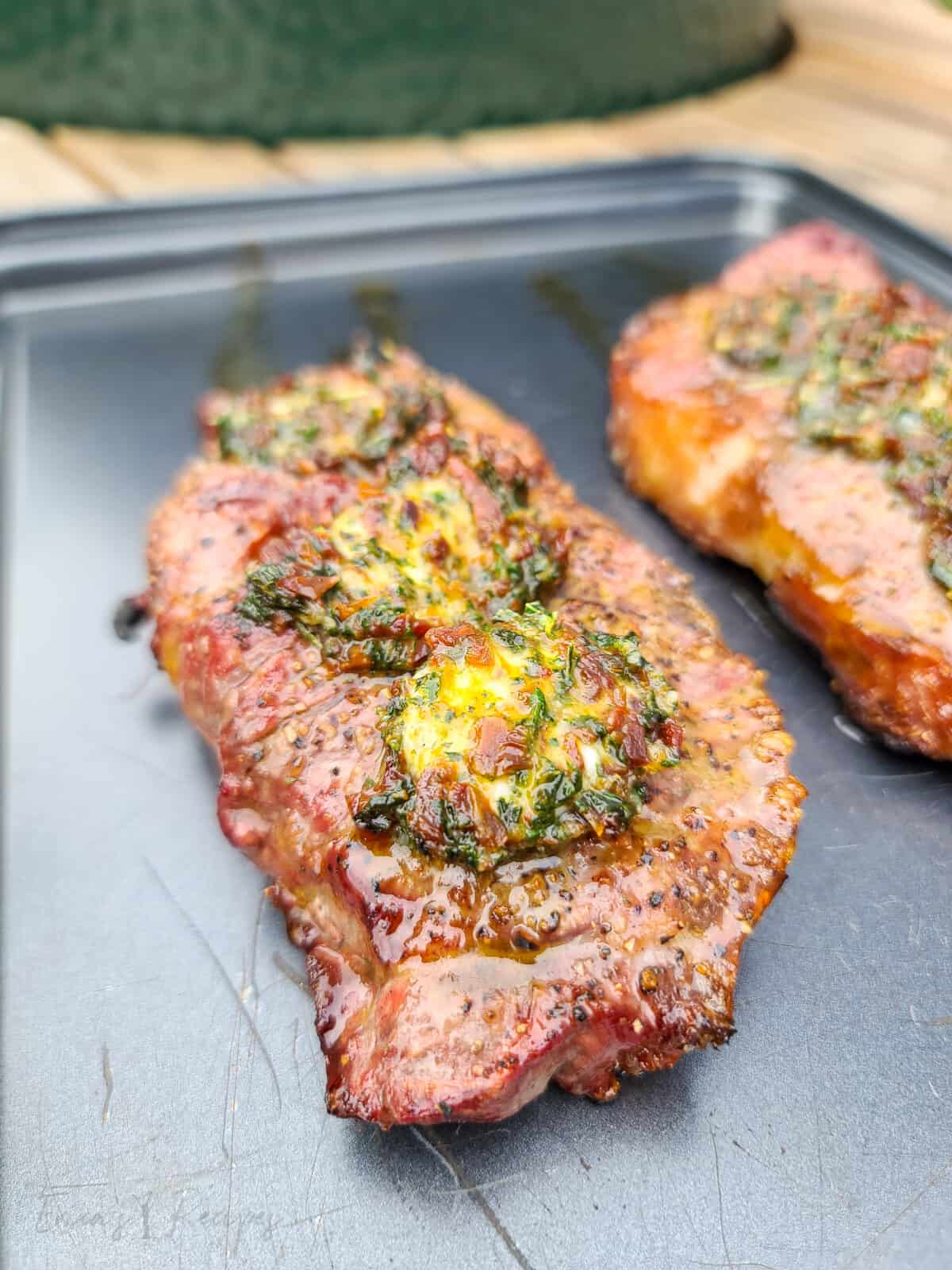 grilled steak on bake sheet topped with sun dried tomato butter