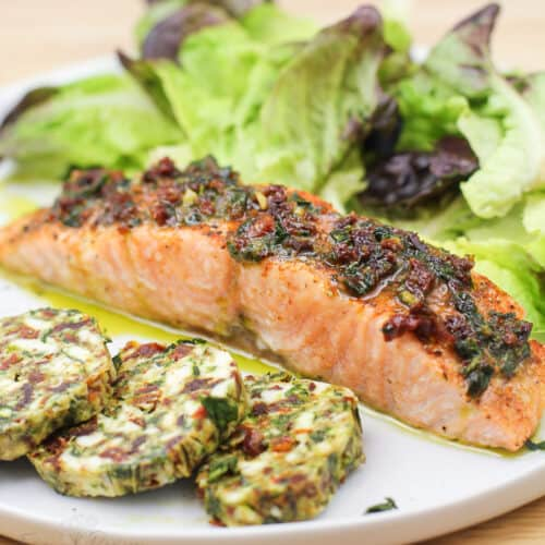 cooked salmon on white plate with salad and finishing butter