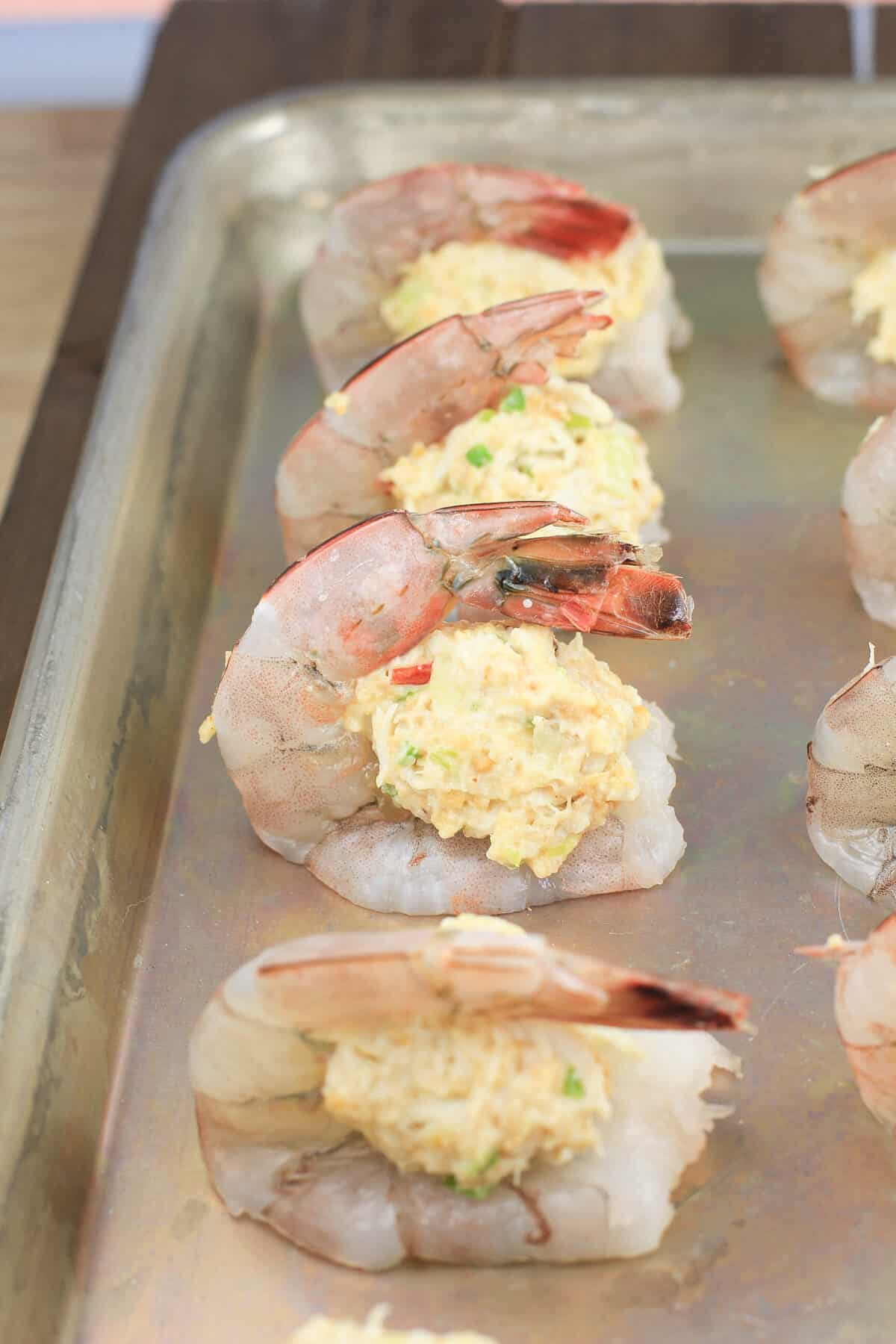crab stuffing on shrimp on bake sheet