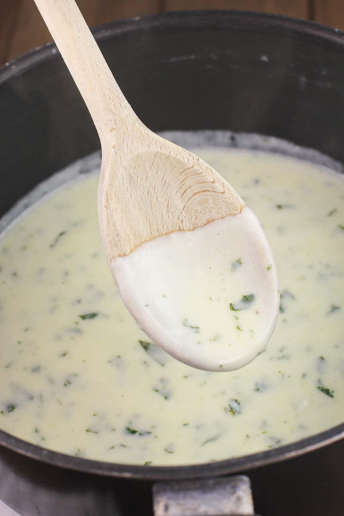lemon basil cream on wooden spoon in saucepan