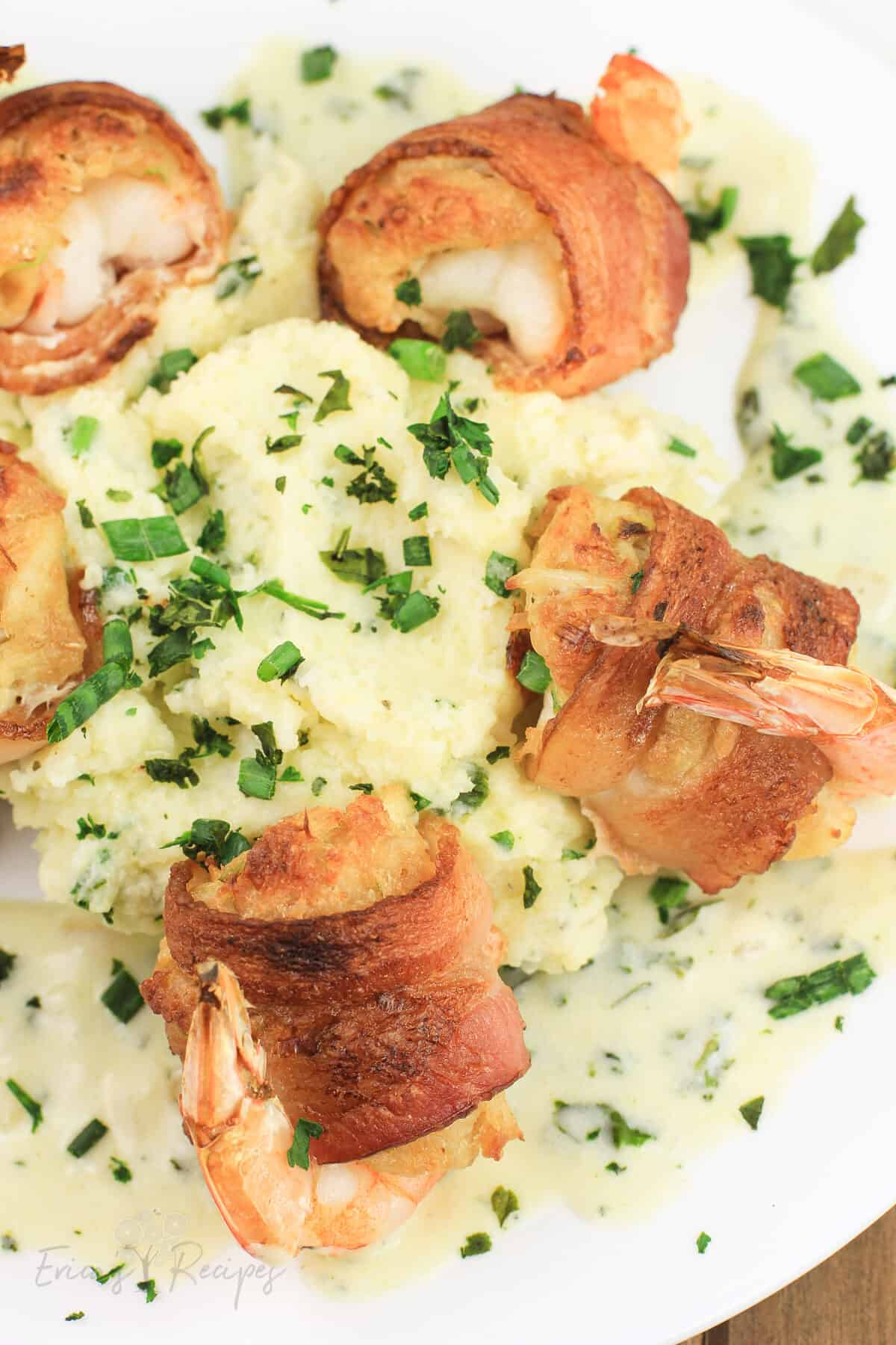 bacon wrapped shrimp on white plate with mashed potatoes