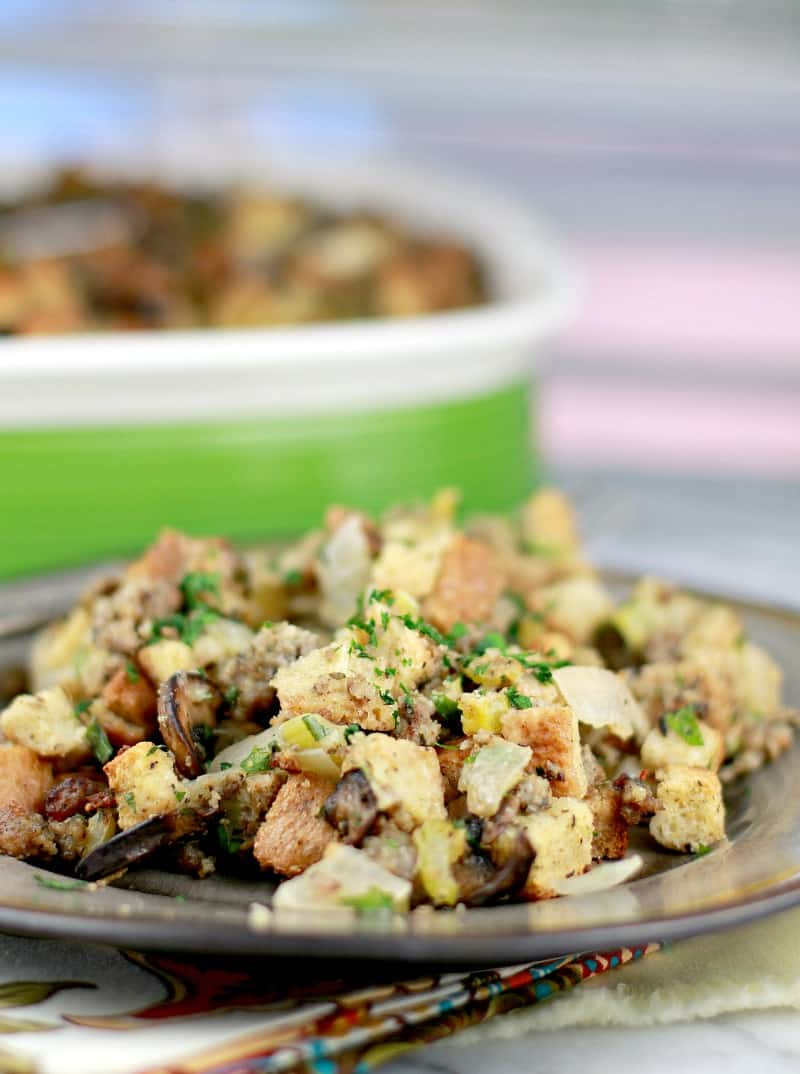 serving of stuffing plated on a brown ceramic plate; casserole in the background