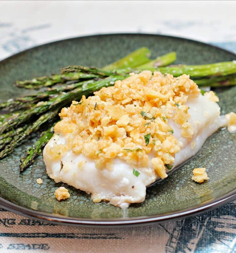 cooked fish topped with cracker stuffing on a green plate with asparagus