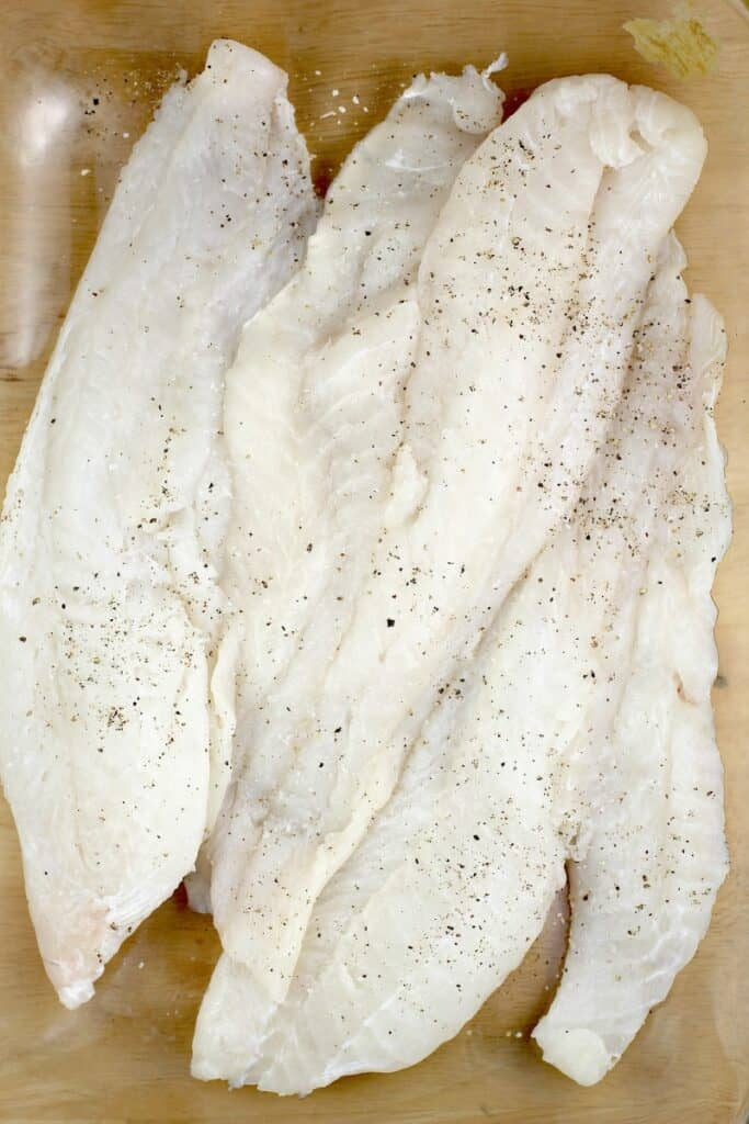 raw cod filets in a clear bake dish