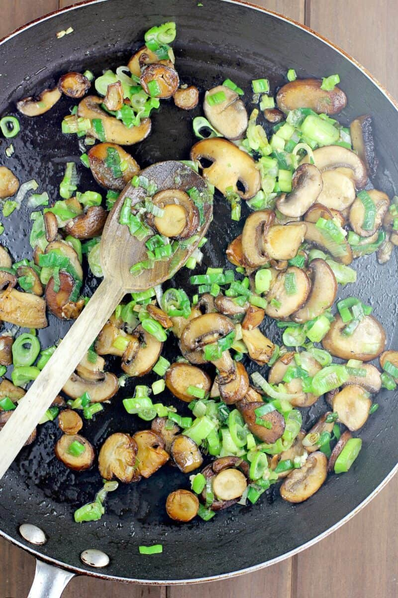 browned mushrooms and green onion with wooden spoon in black skillet