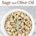 This little recipe for easy white beans is as delightful and flavorful as it is simple and inexpensive to prepare. Creamy white beans simmered in stock with sage and garlic, then tossed in smooth olive oil. Stow this recipe for a quick, vegetarian side dish andsimple accompaniment, or spoon over baked potato or rice as a main course.White Beans with Sage and Olive Oil is a perfect little recipe to have on hand. #food #recipe #whitebeans #tuscanbeans #vegetarianrecipe #vegetariansidedish