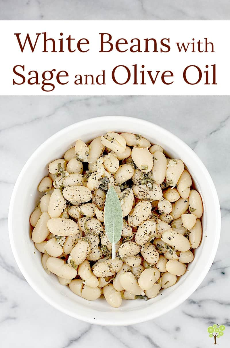 This little recipe for easy white beans is as delightful and flavorful as it is simple and inexpensive to prepare. Creamy white beans simmered in stock with sage and garlic, then tossed in smooth olive oil. Stow this recipe for a quick, vegetarian side dish and simple accompaniment, or spoon over baked potato or rice as a main course. White Beans with Sage and Olive Oil is a perfect little recipe to have on hand. #food #recipe #whitebeans #tuscanbeans #vegetarianrecipe #vegetariansidedish