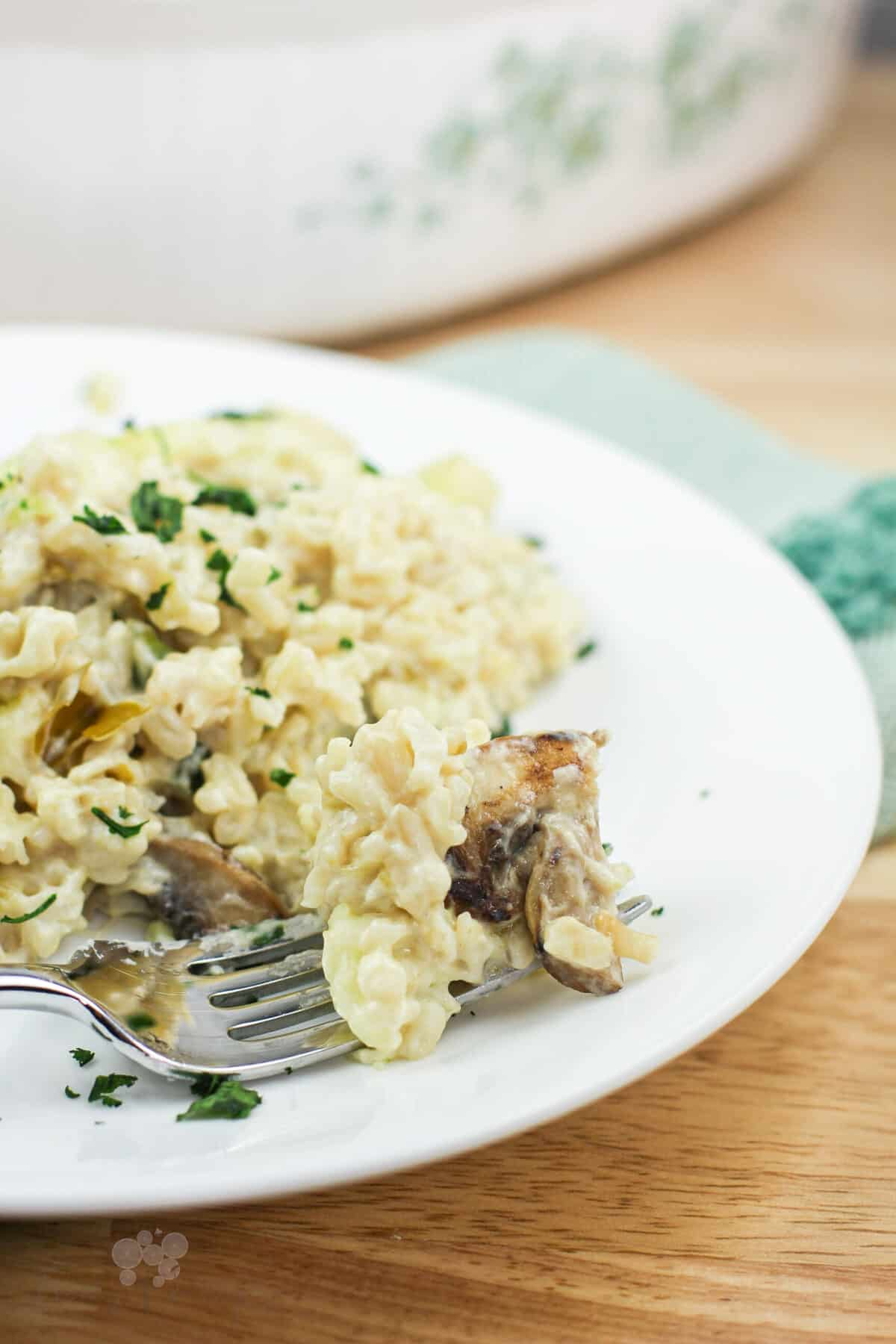 fork on white plate holding a bite-sized amount of rice casserole