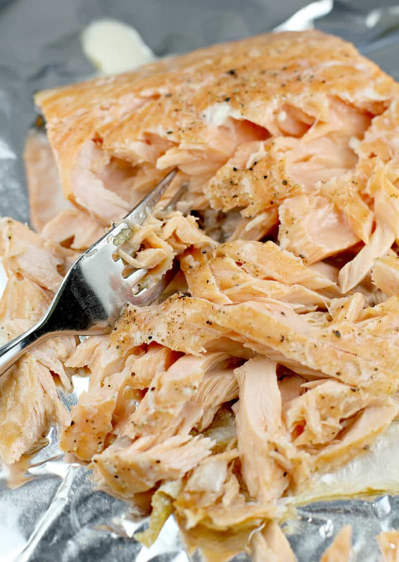 flaked cooked salmon with a fork on a bake sheet