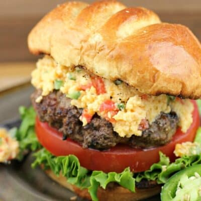 close view of assembled jalapeno pimento cheese burger on a plate, sliced jalapeno on the side