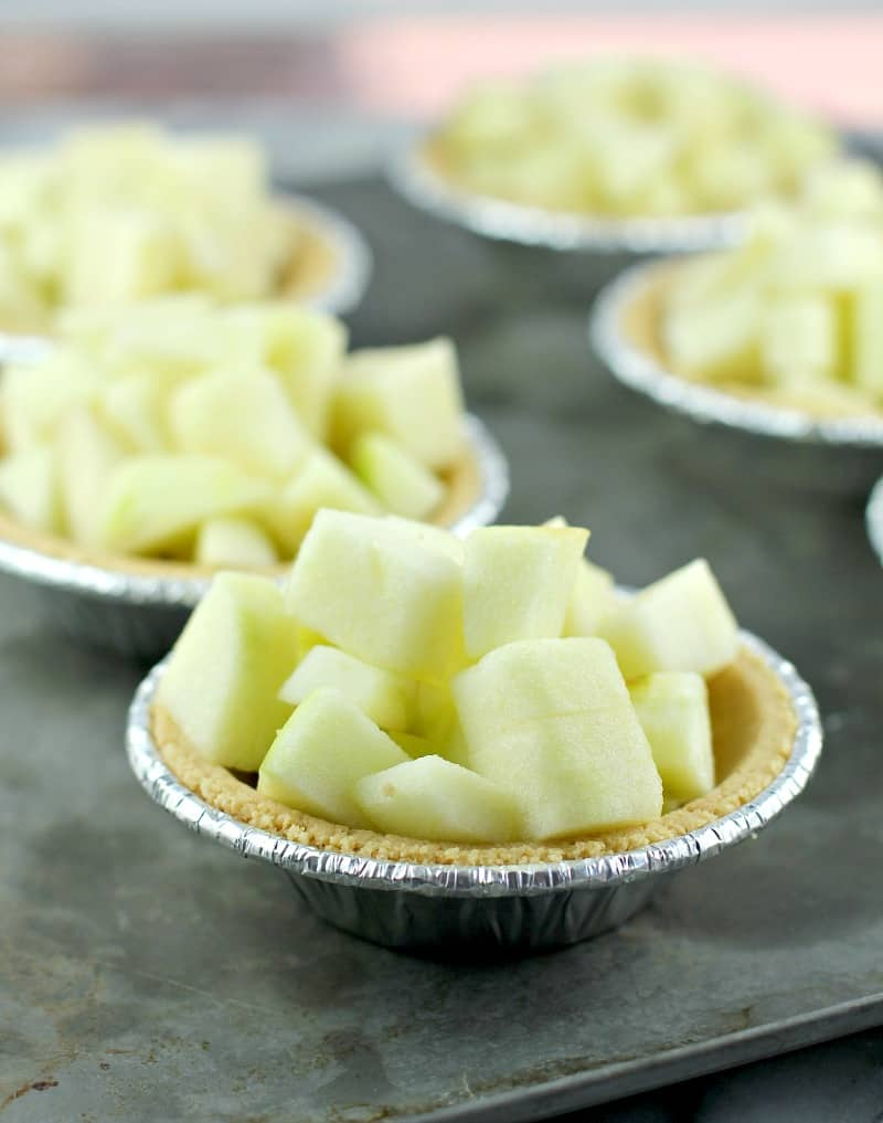 diced apple in a mini graham cracker tart shell on a metal sheet