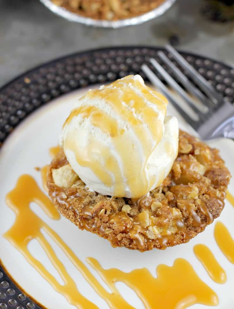 close view of mini apple crisp tart on a plate topped with ices cream and caramel