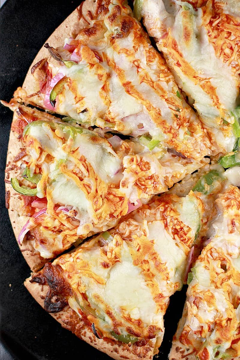 Top down view of this easy recipe with turkey; the finished pizza showing half of the sliced pizza on a black pizza stone.