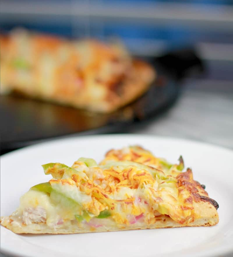 Side view of a slice of pizza on a white plate (green bell pepper, turkey, and onion toppings are peeking out from the cheese); finished pizza is in the background on a black pizza stone