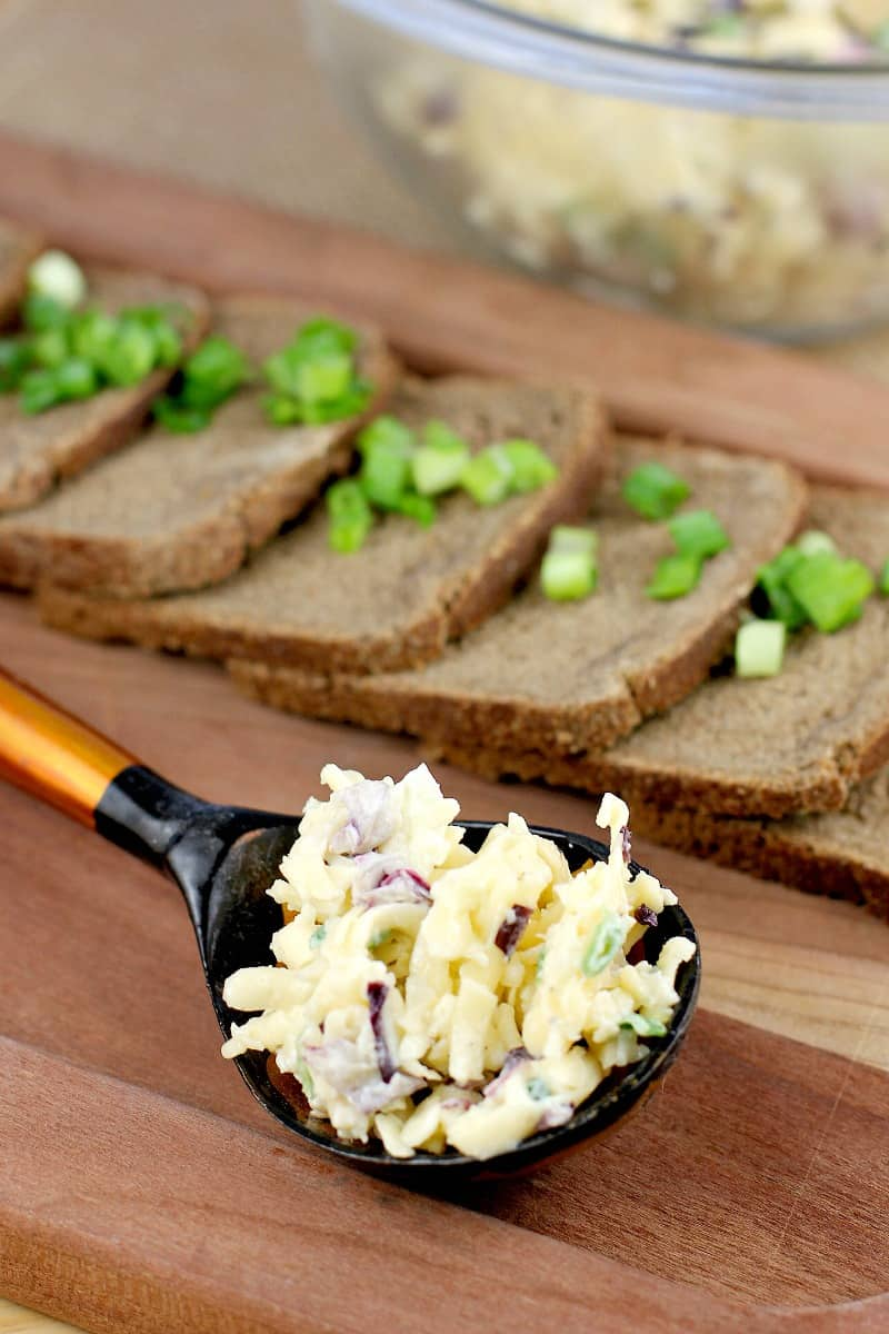 a Russian black and orange spoon holding a mound of this easy appetizer for a party; party bread is in the background