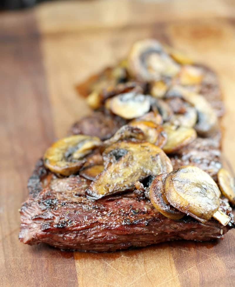 garlic butter skirt steak topped with mushrooms on a wood board