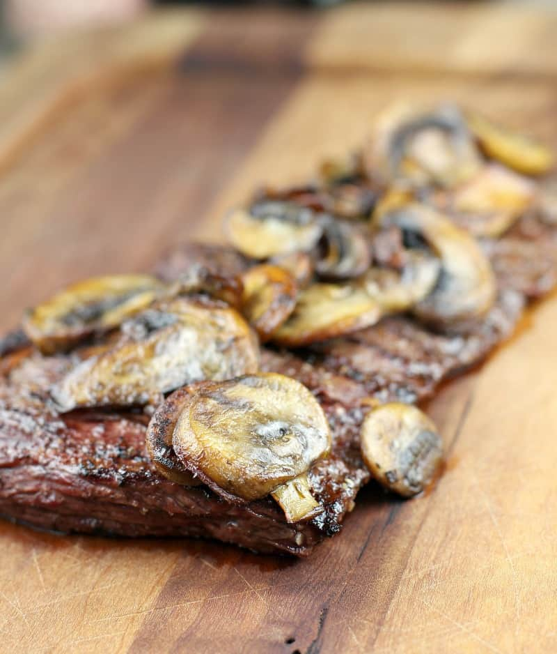 side view of steak on board topped with mushrooms