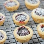 finished cherry cup cookies on a cooling rack over a marble board