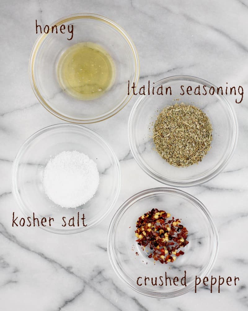 marble board on which are 4 small glass bowls showing ingredients: honey, italian seasoning, salt, and crushed red pepper