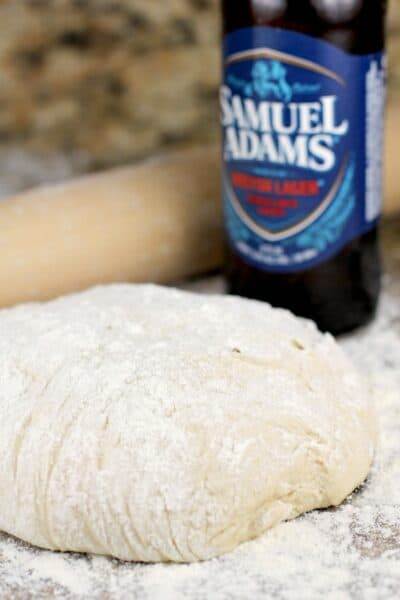 homemade pizza dough on a granite surface with a rolling pin and sam adams beer bottle