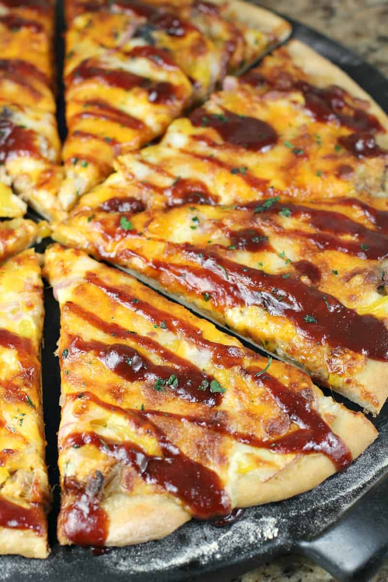 angled view of sliced Texas pizza drizzled with bbq sauce