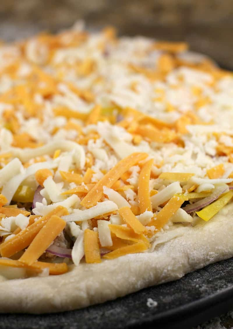cheeses on an uncooked pizza