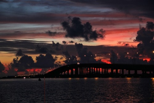 view of a bridge at sunrise over the intercoastal waterway. still dark out with a red sky on the horizon