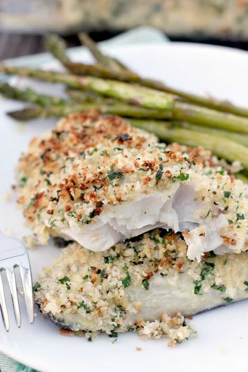 serving of baked haddock with panko on white plate with asparagus and a fork
