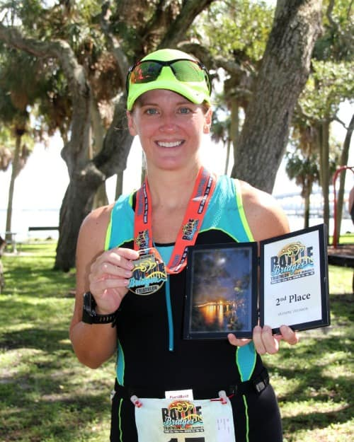picture of the author after a triathlon holding a medal and award