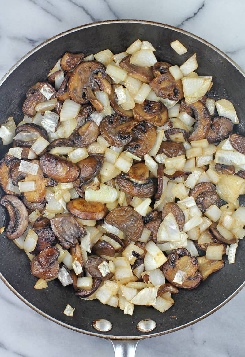 cooked mushrooms and onion in a skillet