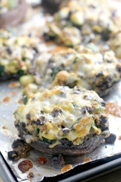 cooked, cheesy stuffed mushrooms on the bake sheet