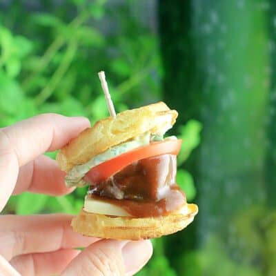 hand holding a meatball sandwiched between mini waffles