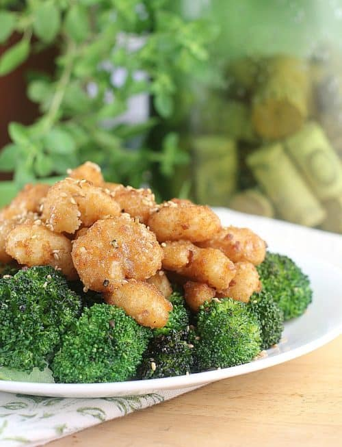 cooked sesame shrimp over broccoli on a white dish