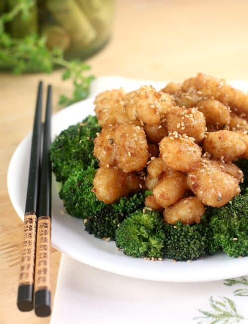 crispy shrimp over broccoli on a white plate with black chopsticks