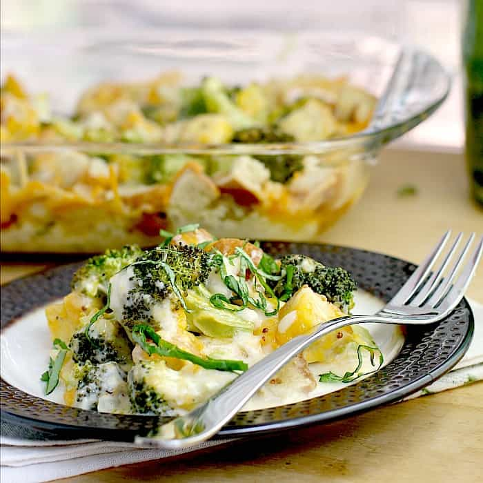 broccoli casserole with cheese on rimmed with with fork. dish is on napkin, on wood surface