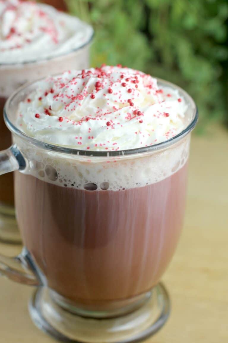 red velvet latte in a glass mug on a wood board; second cup and green leaves of a plant in the background