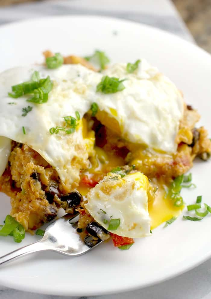 over easy egg on serving of tamale casserole on white plate with fork
