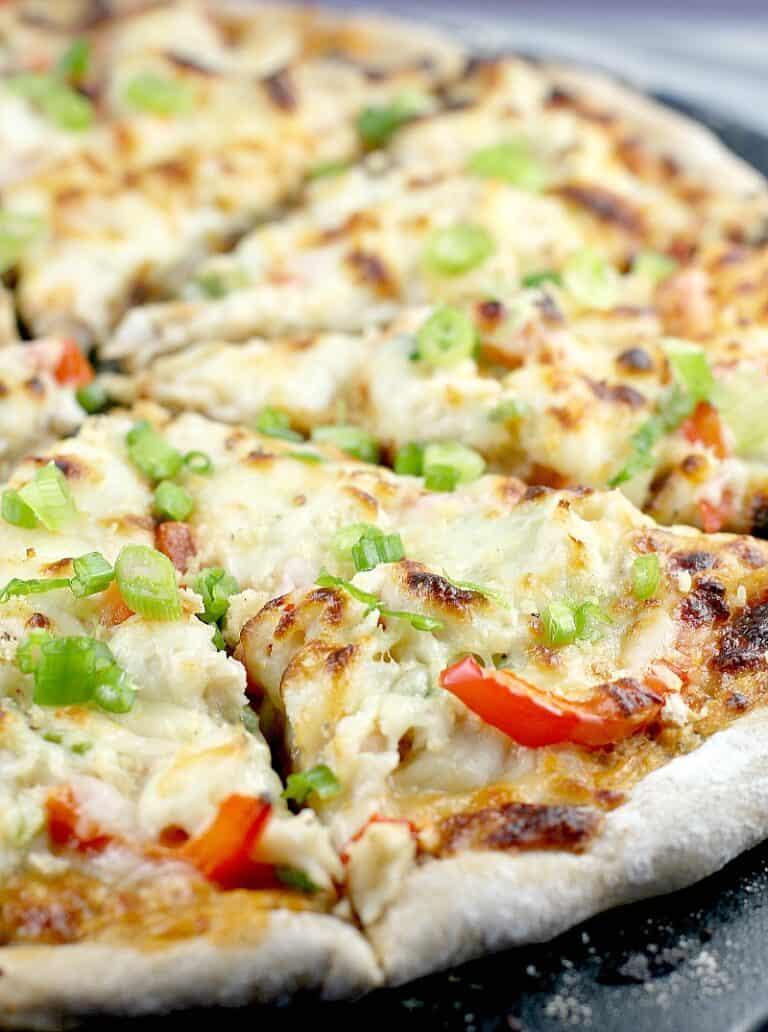 sliced crab rangoon pizza on a black pizza stone